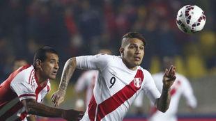 Guerrero, con la camiseta de Perú, pelea por un balón con el...