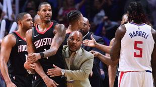 Un miembro del cuerpo técnico de los Rockets sujeta a Trevor Ariza