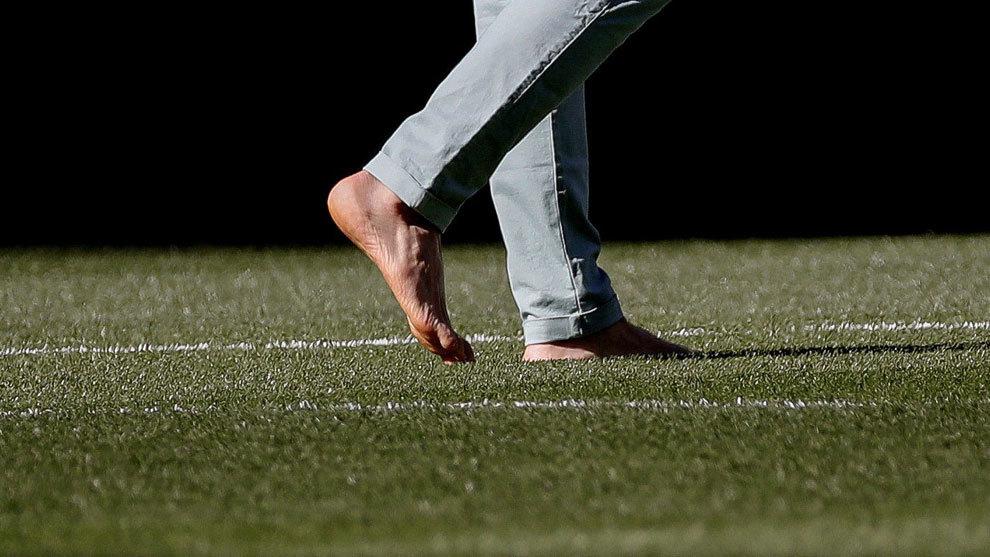 Torres pasea descalzo sobre el césped del Bernabéu.