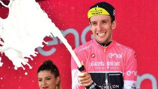 Simon Yates celebrando en el podio su liderato de la general / Daniel...
