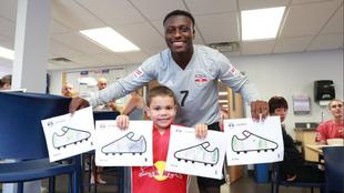 Derrick Etienne junto a un niño y los dibujos de los botines