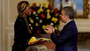 El presidente de Colombia Iván Duque (d) entrega la bandera nacional...