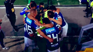 Los jugadores de Millonarios se abrazan con agentes de la Policía.
