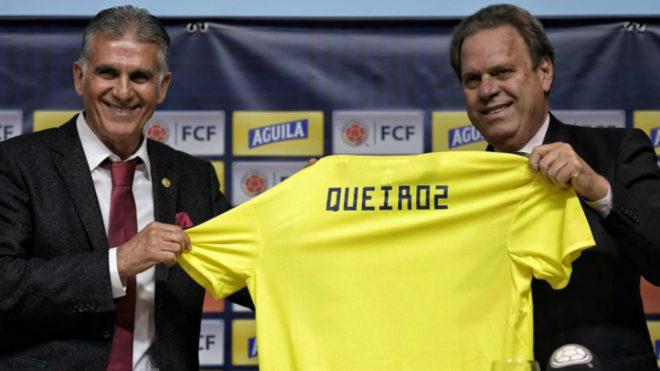 Carlos Queiroz sostiene la camiseta de la Selección Colombia junto a...