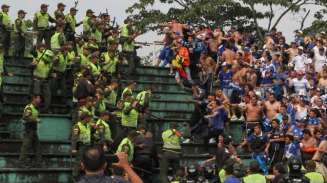 Un grupo de policías se enfrenta a una barra brava de Millonarios.