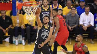 Curry anota ante la mirada de Damian Lillard.