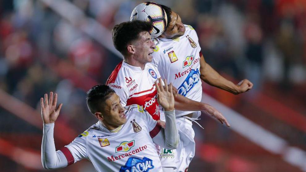 Enzo Yañez (c) de Argentinos Juniors disputa el balón con Diego...