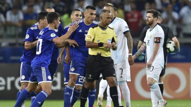 Sampaio recibe las protestas de varios jugadores de Paraguay.