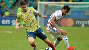 James Rodríguez controla el balón ante la marca de un futbolista...