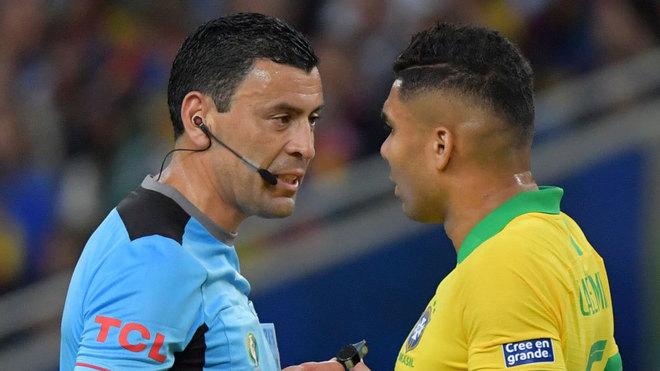 El árbitro Diego Tobar conversa con Casemiro en un momento de la...