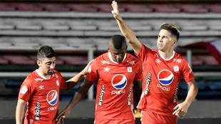 Cristian Alvarez (Der) del América celebra después de anotar el...
