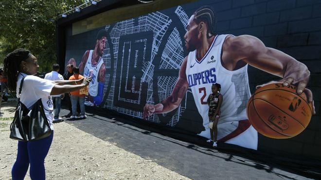 Una pequeña aficionada de los Clippers se toma un foto junto a un...