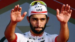 Fernando levanta sus dos manos en un podio.