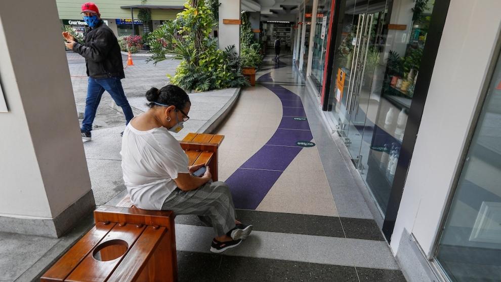 Días sin IVA: mujer sentada en una banca de un centro comercial en...