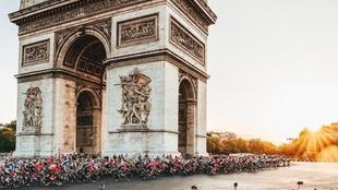 Grupo de ciclistas pasan por el Arco del Triunfo en París.