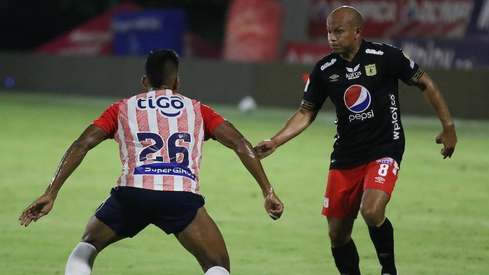 David Murillo del Junior disputa el balón con Juan David Perez del...