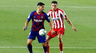 Luis Suárez protege el balón ante la oposición de su compatriota...
