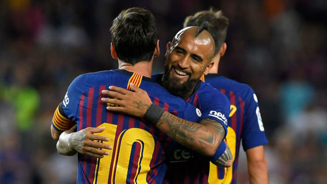 Vidal se abraza a Messi durante un partido del Barcelona