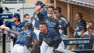 Los jugadores de los Tampa Bay Rays celebran en su cubículo.