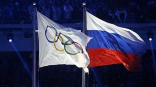 La bandera olímpica ondea junto a la de Rusia durante los Juegos de...