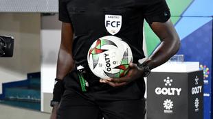 Un árbitro sale al terreno de juego con el balón del fútbol...