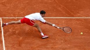 Djokovic intenta devolver una pelota ante Evans.