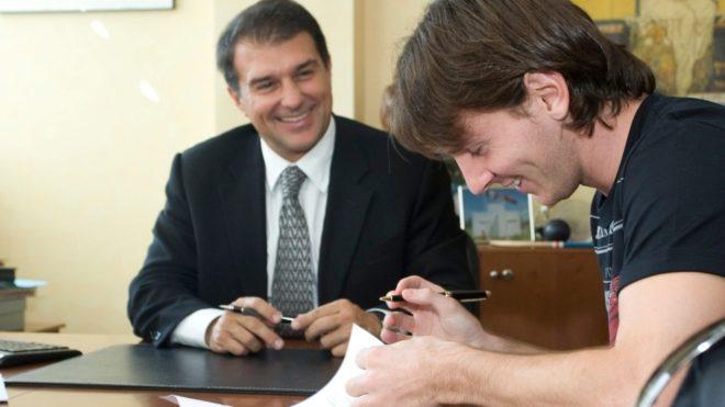Messi firma un contrato con un Laporta sonriente, en una imagen de...