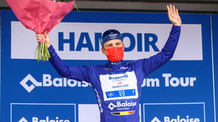 Remco Evenepoel levanta sus manos tras obtener el trofeo.
